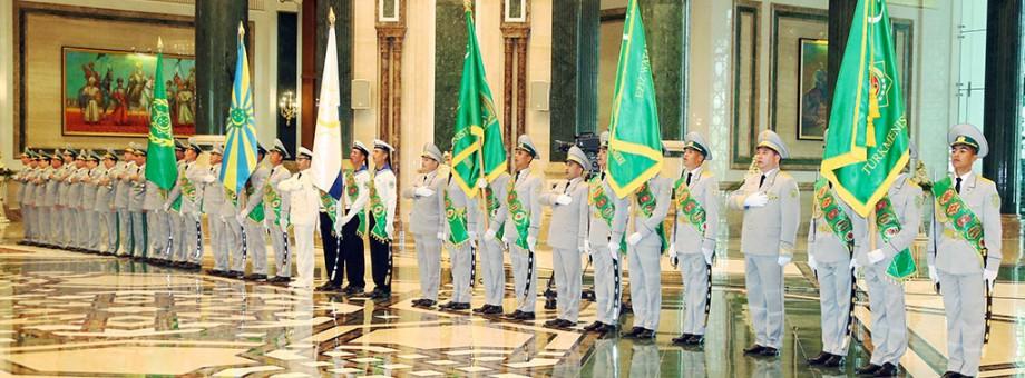 President Gurbanguly Berdimuhamedov hands in the colours to the